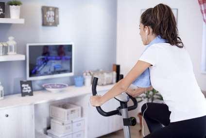 Frau schaut fern während des HeimtrainerTest