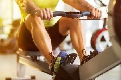 Mann trainiert an Rudergerät im Fitnessstudio