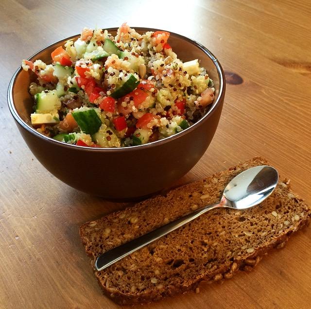 Quinoa Salat in brauner Schüssel mit Scheibe Brot