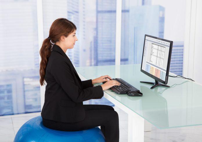 Frau sitzt auf Gymnastikball im Büro
