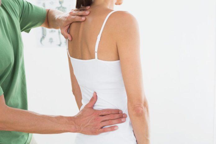 Physiotherapeuten untersucht Frau mit Rückenproblemen
